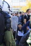 framdelen knäa polispersonen som protesterar Arkivfoto