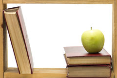 Frame. Some books with dark red hardcover and green apple in a wooden frame on white background Stock Photos