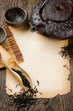 Frame with Asian teapot, dried black tea and vintage paper Stock Photo
