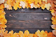 Frame of autumn leaves on a wooden surface. royalty free stock photo