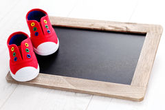 Frame and baby shoes Stock Photos