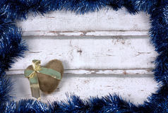 Frame background. With blue garlands and a brown heart with golden ribbon against a white wood background stock images