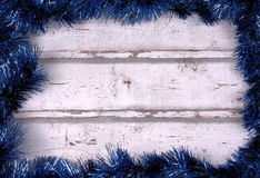 Frame background with blue tinsel garlands. Against a white wooden background stock images