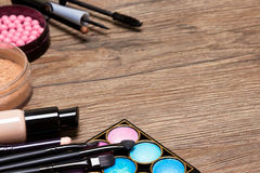 Frame of basic makeup products with copy space. Frame of basic makeup products on wooden surface with copy space. Concealer, bottle of foundation, powder, blush royalty free stock photography