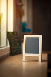 A-frame black board on wood bar. Small A-frame black board with blank area for text or message on wood bar in cafe wih low key scene Stock Photos