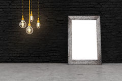 Frame on black brick. Blank picture frame and light bulbs in interior with black brick wall and concrete floor. Mock up, 3D Rendering Royalty Free Stock Photo