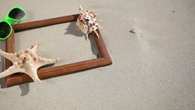 Frame blank with seashell, starfish and sunglasses on the beach Royalty Free Stock Image