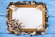 Frame with a blank sheet for inscription on a blue wooden background of gorshkov stones and seashells stock photography