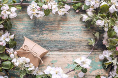 Frame of blossoming apple tree branches with gift boxes on woode Stock Photo