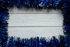 Frame from a blue Christmas garland. Wooden white background. Retro Royalty Free Stock Image