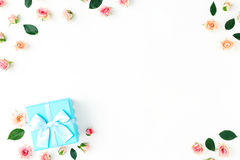Frame of blue gift box and pink roses flat lay Royalty Free Stock Image