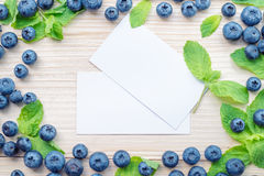 Frame of blueberries and mint leaves on a light wooden table. Healthy breakfast with vital vitamins. Two white cards for text in a center Royalty Free Stock Photo