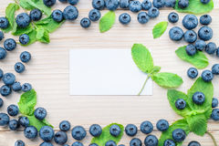 Frame of blueberries and mint leaves on a light wooden table. Healthy breakfast with vital vitamins. White card for text in a center Stock Photos