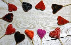 Frame border of Handmade felt hearts on light wooden background. Royalty Free Stock Photos