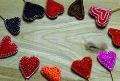 Frame border of Handmade felt hearts on light wooden background. Royalty Free Stock Images