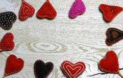 Frame border of Handmade felt hearts on light wooden background. royalty free stock photos