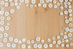 Frame border made of vintage buttons on wooden background. Frame border made of old vintage buttons on wooden table. Copy space for text royalty free stock photo