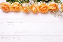 Frame or border from peach color roses flowers on white wooden. Background. Shubby chic. Place for text.Selective focus.Top view stock image