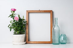 Frame, bottles and rose. Vintage blank wooden frame, bottles and rose in a pot on a white wall Stock Photography
