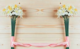 Frame of bouquets of daffodils flowers tied with pink ribbon on a natural wooden background with copy space Stock Image