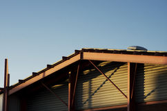 Frame bracing on warehouse roof and wall during sun set.  Stock Images