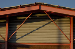 Frame bracing on warehouse roof and wall during sun set.  Stock Photo