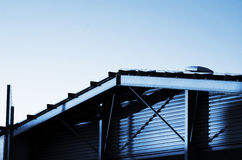 Frame bracing on warehouse roof and wall during sun set.  Stock Photos
