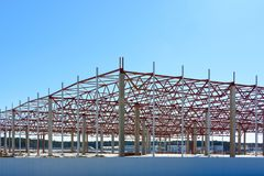 The frame of the building during the construction of a large shopping center store warehouse logistics center. The frame of the building during the construction stock photo