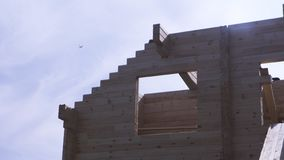 Frame of building, wooden log house on blue sky background with a plane flying away. Construction in progress of a royalty free stock image