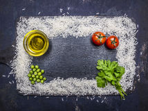 Frame, built of white rice with butter, pepper, parsley and cherry tomatoes place for text,frame wooden rustic background top v Royalty Free Stock Photo