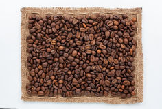 Frame of burlap and coffee beans lying on a white background Royalty Free Stock Images