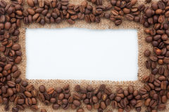 Frame of burlap and coffee beans lying on a white background. Can be used as texture Stock Photography