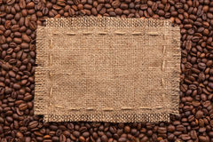 Frame of burlap and coffee beans lying on a white background. With place for your text Royalty Free Stock Image