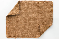 Frame of burlap with curled edges, lies on a white background Royalty Free Stock Photography