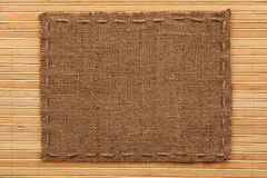 Frame of burlap, lies on a background of  bamboo mat Stock Images