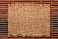 Frame of burlap, lies on a background of  bamboo mat Stock Photo