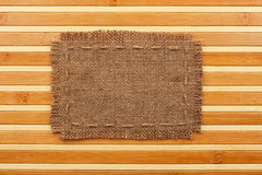 Frame of burlap, lies on a background of  bamboo mat Royalty Free Stock Images