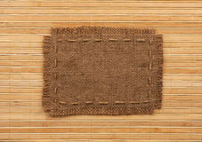 Frame of burlap, lies on a background of  bamboo mat Stock Image