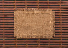 Frame of burlap, lies on a background of  bamboo mat Royalty Free Stock Image
