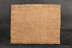 Frame of burlap, lies on a background of black leather Stock Photo