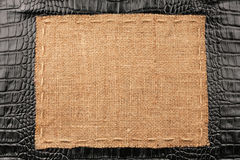 Frame of burlap, lies on a background of black leather Royalty Free Stock Image