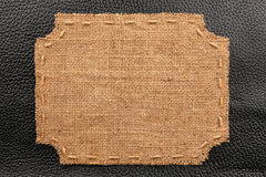 Frame of burlap, lies on a background of black  leather Stock Image
