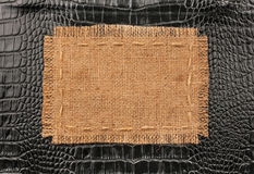 Frame of burlap, lies on a background of black leather Royalty Free Stock Images