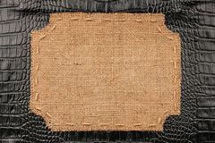 Frame of burlap, lies on a background of crocodile leather Stock Image