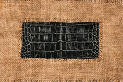 Frame of burlap, lies on a background of crocodile leather Stock Photography