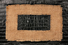 Frame of burlap, lies on a background of crocodile leather Stock Photo