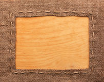 Frame of burlap, lies on a background of wood Stock Photography