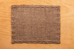 Frame of burlap, lies on a background of wood Stock Photos