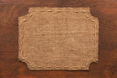 Frame of burlap, lies on a background of wood Royalty Free Stock Photo