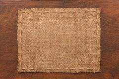 Frame of burlap, lies on a background of wood Royalty Free Stock Photography
